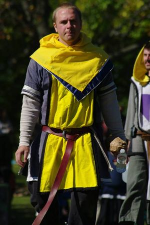 This marshal is wearing a yellow tabard and a yellow cowl that can be worn over other garb.